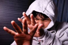 Man with Hood pushing away with his hands, repulsion with stopping hand gesture, Stock Image
