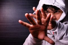 Man with Hood pushing away with his hands, repulsion with stopping hand gesture, Royalty Free Stock Photos