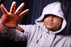 Man with Hood pushing away with his hands, repulsion with stopping hand gesture, Stock Photo