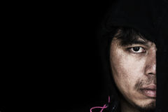 Man in hood with scary face. In the dark stock photo