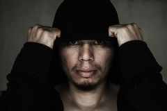 Man in hood with scary face. In the dark royalty free stock image