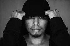 Man in hood with scary face in the dark Royalty Free Stock Image