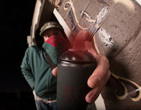 Man with Hood and Spray Paint Stock Images