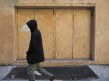 Man with hood walking by double doors Royalty Free Stock Photography