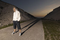 Man In Hooded Sweatshirt On Deserted Road. Full length portrait of a young man wearing hooded sweatshirt in the middle of a deserted road Stock Images