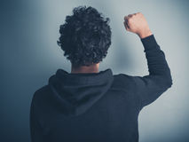 Man in hooded top raising his fist. Rear view shot of a young man in a hooded top raising his fist in the air Stock Photos