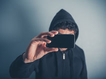 Man in hooded top taking photos Stock Photography