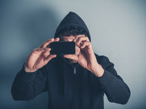 Man in hooded top taking photos Royalty Free Stock Photo