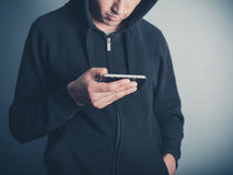 Man in hooded top using his smartphone Stock Photography
