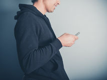 Man in hooded top using his smartphone Royalty Free Stock Photo