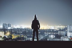 Man in hoodie in Bangkok. Back view of young person in hoodie on night Bangkok city background. Success, research and leadership concept stock image