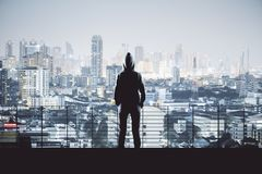 Man in hoodie in Bangkok. Back view of young person in hoodie on night Bangkok city background. Success, vision and leadership concept stock photo