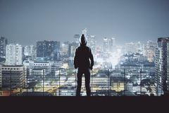 Man in hoodie in Bangkok. Back view of young person in hoodie on night Bangkok city background. Success, winner and leadership concept stock image