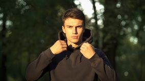 Man in hoodie confidently looking at camera, ready to start new life, decision. Stock photo royalty free stock photography