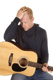 Man in hoodie with guitar look down hand on head Royalty Free Stock Photography