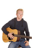 Man in hoodie with guitar look serious Royalty Free Stock Images