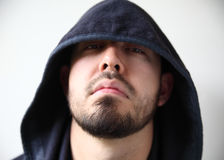 Man in hoodie looks hostile. Young man with dark hood hiding part of his face royalty free stock image