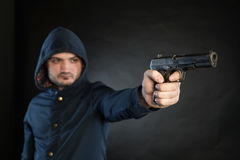 Man in a hoodie is pointing a handgun at the target. Royalty Free Stock Image