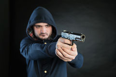 Man in a hoodie is pointing a handgun at the target. Stock Photos