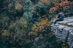 Man In Hoodie Sitting On Rock Cliff Stock Photography