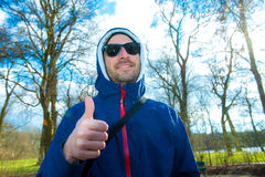 Man with hoodie sweater with thumb up Stock Images