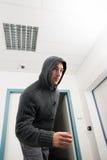 Man in hoodie walking under cctv surveillance area Stock Images