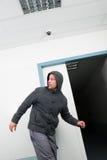 Man in hoodie walking under cctv surveillance area Stock Photo
