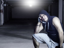 Man with hoodie. Young handsome man with hoodie in industrial garage looking at camera and resting head on arm Royalty Free Stock Photos