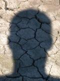 Man hoofdschaduw op droge aarde stock afbeelding