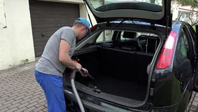 Man hoover car boot with vacuum cleaner. stock video footage