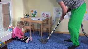 Man hoover child room and little girl play with tablet computer sitting on floor stock footage