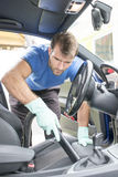 Man hoovering the car cabin, cleaning concept. Stock Photos