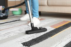 Man hoovering carpet with vacuum cleaner. At home royalty free stock photo