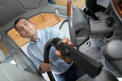 Man hoovering seat car during car cleaning Royalty Free Stock Images