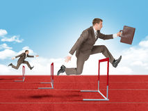 Man hopping over red treadmill barrier Stock Photos