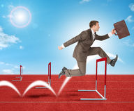 Man hopping over treadmill barrier Stock Photo