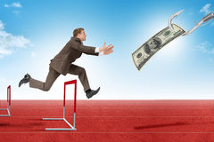 Man hopping over treadmill barrier with dollar Stock Images