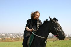 Man on a horse. The man with long hair on a black horse Royalty Free Stock Image