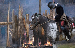 Man on horse after battle. Man on horse after medieval battle, wooden house on fire behind Stock Photo
