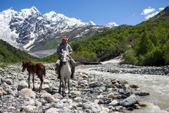 Man on a horse crossing a river in Georgia. Man on a horse crossing a river in Caucasus mountains in Svaneti, Georgia royalty free stock images