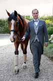Man and horse. Man dressed in an elegant cut  with his horse in front of a house, waiting for the bride Stock Images