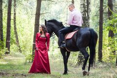 Man on horse and girl. Young beautiful brunette girl in red dress walk and handsome men in pink shirt ride on the black horse in green forest Stock Photography