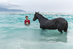 Man with horse in sea Royalty Free Stock Photo