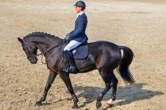 Man horseback riding on black beautiful horse. Young male jockey with horseback riding equipment, riding on black purebreed race horse Royalty Free Stock Images
