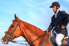 Man horseback riding on brown horse. Young male jockey with horseback riding equipment, riding on purebreed race horse Stock Image