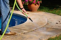 Man hosing pool paving, Spain. stock images