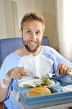 Man in hospital room eating healthy diet clinic food in happy satisfied face expression Royalty Free Stock Images