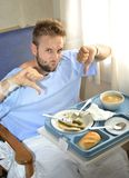 Man in hospital room eating healthy diet clinic food in upset moody face expression Stock Photo
