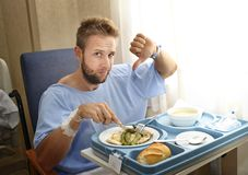 Man in hospital room eating healthy diet clinic food in upset moody face expression Royalty Free Stock Photos