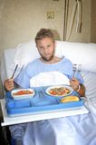 Man in hospital room eating healthy diet clinic food in upset moody face expression. Young man in hospital room after suffering accident eating healthy Stock Photography